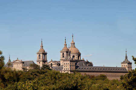 San Lorenzo de El Escorial Monastery from Casita del Infante. The towers of the church and monastery are set of by a bright blue sky. 에디토리얼