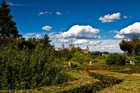 San Lorenzo de El Escorial Monastery from Casita del Infante. The towers of the church and monastery are set of by a bright blue sky. Stock Photo