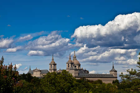San Lorenzo de El Escorial Monastery from Casita del Infante. The towers of the church and monastery are set of by a bright blue sky. Editorial