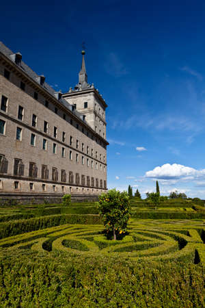 San Lorenzo de El Escorial Monastery with its formal gardens. The towers of the monastery are set of by a bright blue sky with a few white clouds.