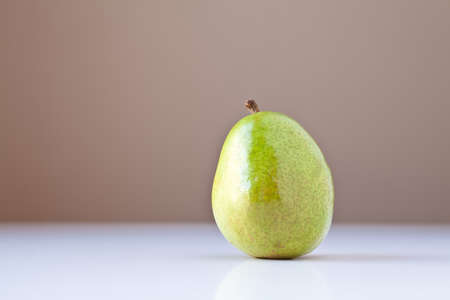 Single green pear on white table with taupe brown background. The concepts depicted in this image are nutrition, good food choices, balanced diet and good for you.