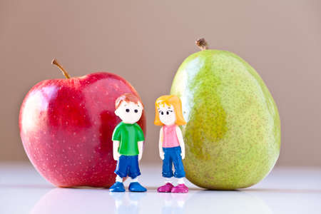 Toy girl and boy discuss nutrition and healthy choices in front of a green pear and a  red apple. The concepts depicted in this image are nutrition, good food choices, balanced diet and good for you. Stock Photo