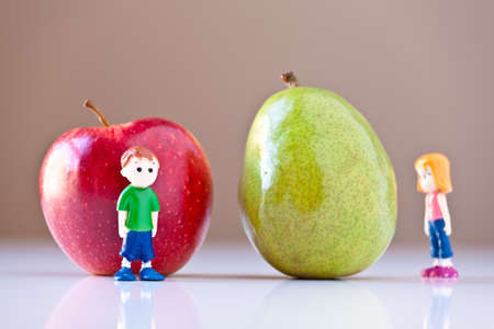 Toy girl and boy disagree over nutrition and healthy choices in front of a green pear and a  red apple. The concepts depicted in this image are nutrition, good food choices, balanced diet and good for you.
