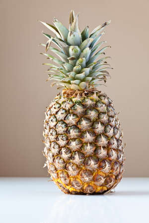 Single partially ripened pineapple on white table with taupe brown background. The concepts depicted in this image are nutrition, good food choices, balanced diet and good for you.