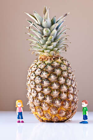 Toy girl and boy are overwhelmed by nutrition and healthy choices next to a giant pineapple. The concepts depicted in this image are nutrition, good food choices, balanced diet and good for you.