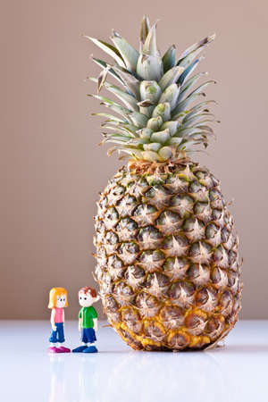 Toy girl and boy discuss nutrition and healthy choices next to a giant pineapple. The concepts depicted in this image are nutrition, good food choices, balanced diet and good for you.