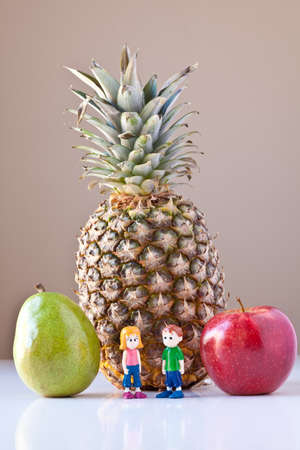 Toy girl and boy standing in front of pineapple, red apple and green pear on white with taupe brown background. The concepts depicted in this image are nutrition, good food choices, balanced diet and good for you.