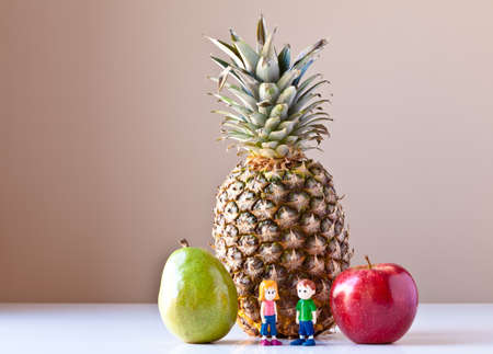 Toy girl and boy overwhelmed by making good food choices. They are standing in front of pineapple and between green pear and red apple. The concepts depicted in this image are nutrition, good food choices, balanced diet and good for you.