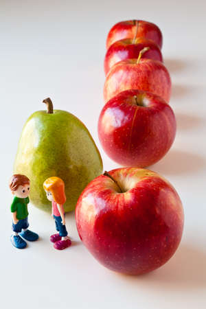 Toy girl and boy discuss nutrition and healthy choices in front of green pear standing out from a line of red apples. The concepts depicted in this image are nutrition, good food choices, balanced diet, good for you, being different, unique, stick out, be