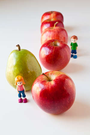 Toy girl and boy overwhelmed by making good food choices. Green pear standing out from a line of red apples. The concepts depicted in this image are nutrition, good food choices, balanced diet, good for you, being different, unique, stick out, being singl