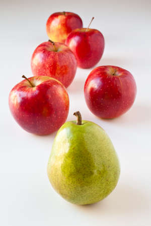 Green pear leading a group of red apples. The concepts depicted in this image are nutrition, good food choices, balanced diet, good for you, being different, unique, stick out, being singled out, leading by example.