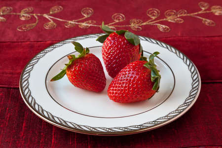 Three red strawberries with green leaves on a white fine china plate with silver decoration on the rim. Red textured background.