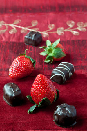 Dark chocolate bon-bons and strawberries on red textured background. photo
