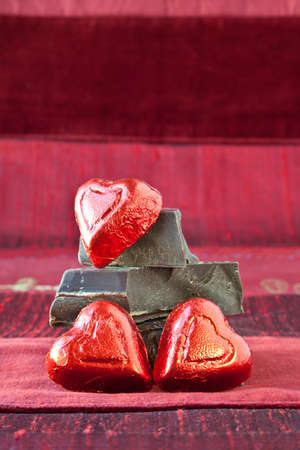 Red foil wrapped candy hearts arranged on top of pile of gourmet thick dark chocolate bar chunks. Red textured background. Stock Photo