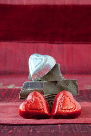 Two red and one silver foil wrapped candy hearts arranged on top of pile of gourmet thick dark chocolate bar chunks. Red textured background. Concept: third wheel, odd man out, does not fit in. Stock Photo