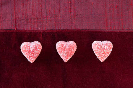 Three jelly (gummy) sugar coated candy hearts in a row on red textured background.