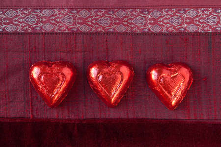 Three red foil wrapped candy hearts in a row on red textured background.