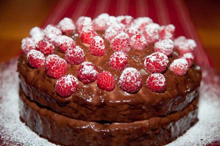 Hele lekkere verjaardagstaart met chocolade ganache en frambozen met een laagje poedersuiker.