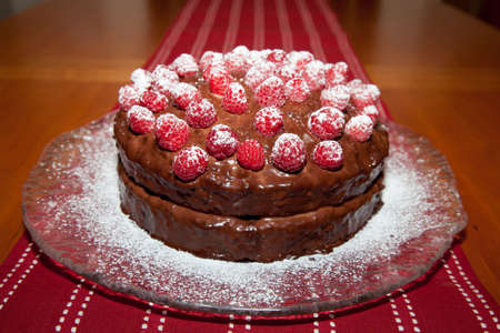 Whole delicious birthday cake with chocolate ganache and raspberries with dusting of powdered sugar.