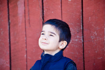 Little boy looking up and to the left in front of red textured background with a joyfull day dreaming expression. Stock Photo