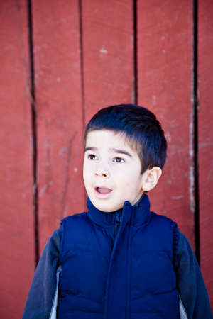 Little boy looking up and to the left in front of red textured background with a surprised and amazed expression.