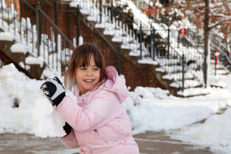 Winter portrait of a smiling little girl playing in the snow throwing a big snow ball.