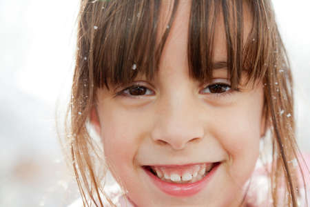 Closeup portrait of a smiling happy little girl with snow flakes in her hair Stock Photo