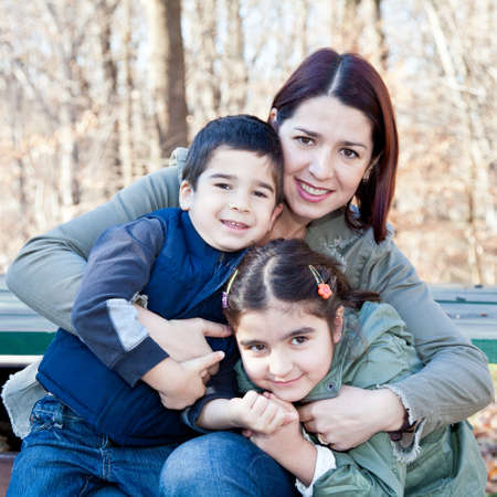 Family portrait of a smiling mother hugging a boy and girl. Stock Photo