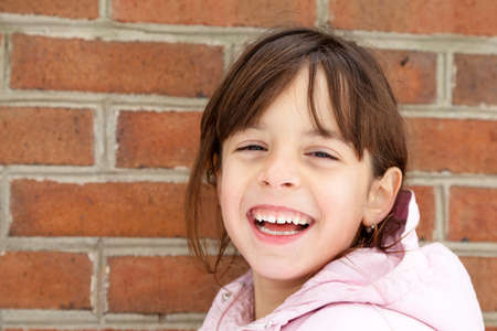 Laughing little girl in winter jacket in front of a brick wall