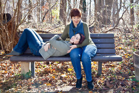 Mother holding her daughter on a park bench.