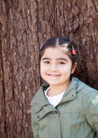 Portrait of a smiling happy little girl in front of a tree with bark texture in the background 스톡 사진