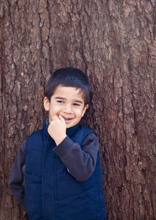 Little boy looking to the left in front of a tree with bark texture in the background biting on his finger with a shy expression.