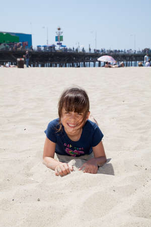 Little girl relaxing on the beach and playing with sand.