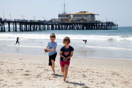 Little girl and boy running on the beach and playing with wet sand. Editorial