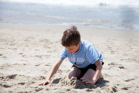 Little boy playing with sand on the beach.