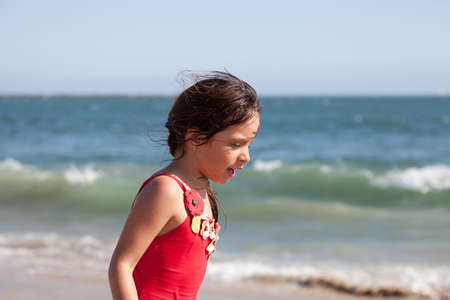 Little girl walking and talking on the beach with the ocean and waves in the background.