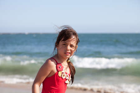 Little girl with a puzzled and surprised expression on the beach by the ocean.