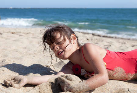 ビーチに出かける小さな女の子は砂で覆われて。彼女は、彼女は目を閉じてリラックスしています。