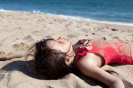 Little girl hanging out on the beach covered in sand. Closeup of a sleeping girl on the beach with ocean in the background