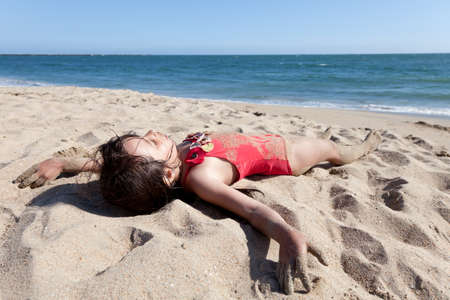 nap: Little girl hanging out on the beach covered in sand. Sleeping girl in red bathing suit on the beach with ocean and sky in the background