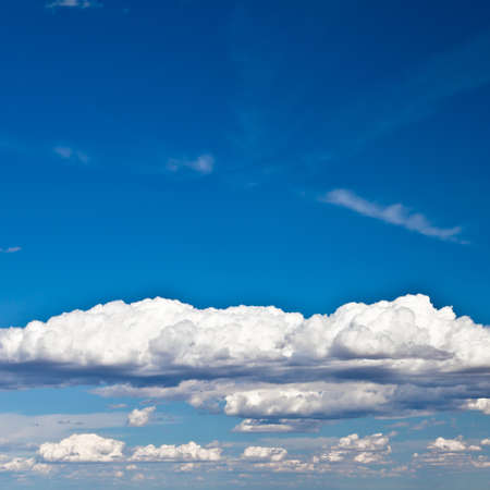 Blue summer sky with low white clouds with copy space