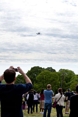 u s: April 17, 2012 - Washington, DC, U S  Space shuttle Discovery, mounted on the Shuttle Carrier Aircraft, has flown over the Washington, D C  area  Onlookers are watching the final flight and taking pictures