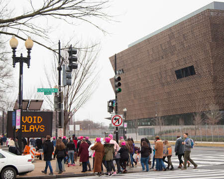 Women and men of all ages donning pink hats crossing Constitution Avenue with the new African American Museum in the background to reach the rally site to protest President Trumps positions on womens and other human rights.