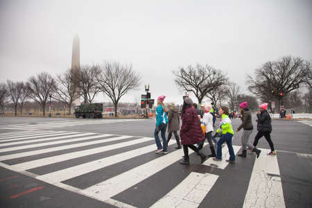 Group of women crossing the street on Constitution Avenue with the Washington Monument bathed in fog in the background to make their way to the rally to protest President Trumps positions on womens and other human rights.