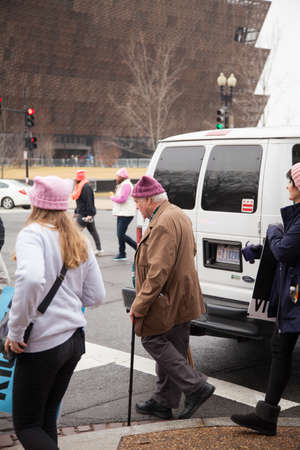 Older man with a walking cane donning a pink hat crossing Constitution Avenue with the new African American Museum in the background to reach the rally site to protest President Trumps positions on womens and other human rights. Credit: Dasha RosatoAla