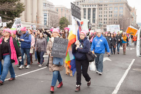 Women carrying signs and flags protested President Trumps positions on womens and other human rights.