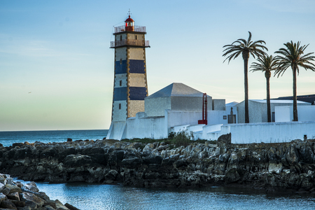 lighthouse with sea view and palm trees in Cascais Portugal Stock Photo
