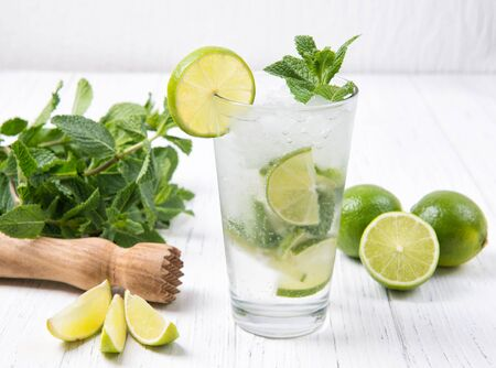 Mojito cocktail with fresh limes and mint leaves in a glass on a light gray stone background