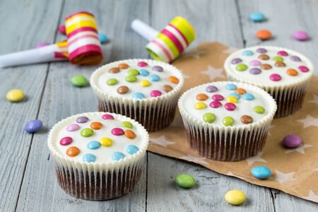 Chocolate cupcakes glazed with smarties, wooden background