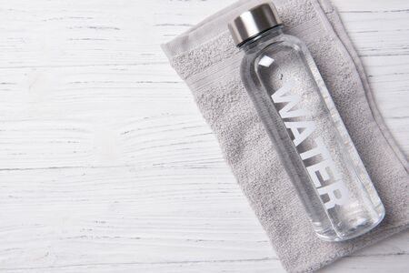 Bottle of water with word water on it on the gray towel, healthy life concept